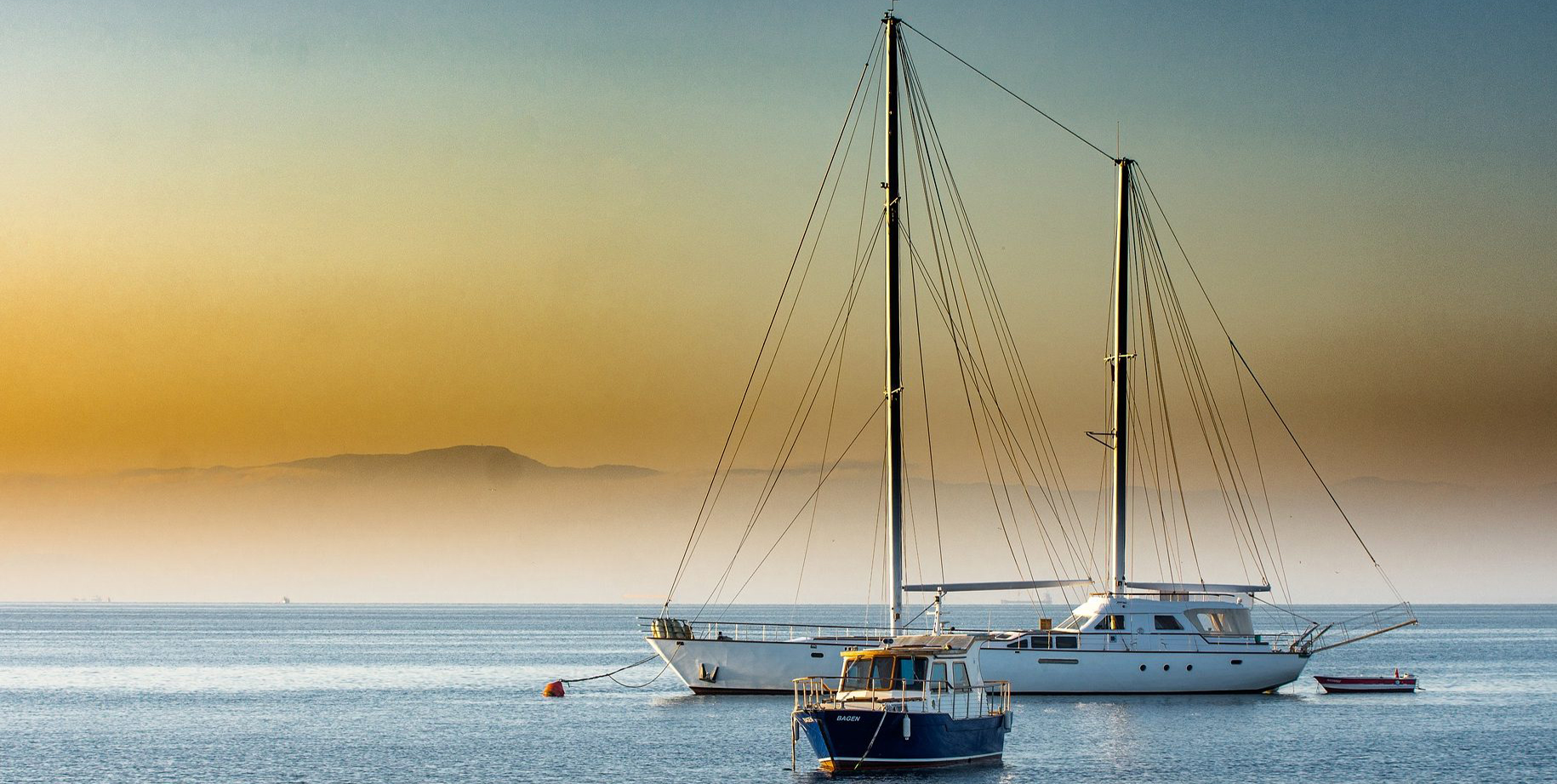 Yacht at anchor & small fishing vessel at anchor on a misty morning at sunrise