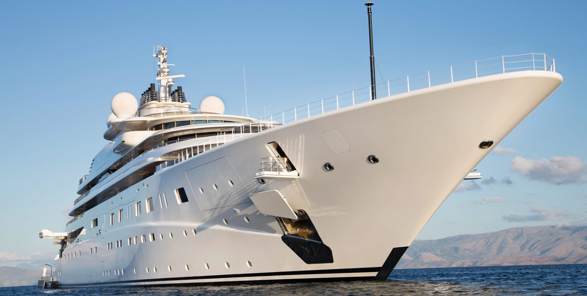 Megayacht at sea on a clear day with mountains in the background
