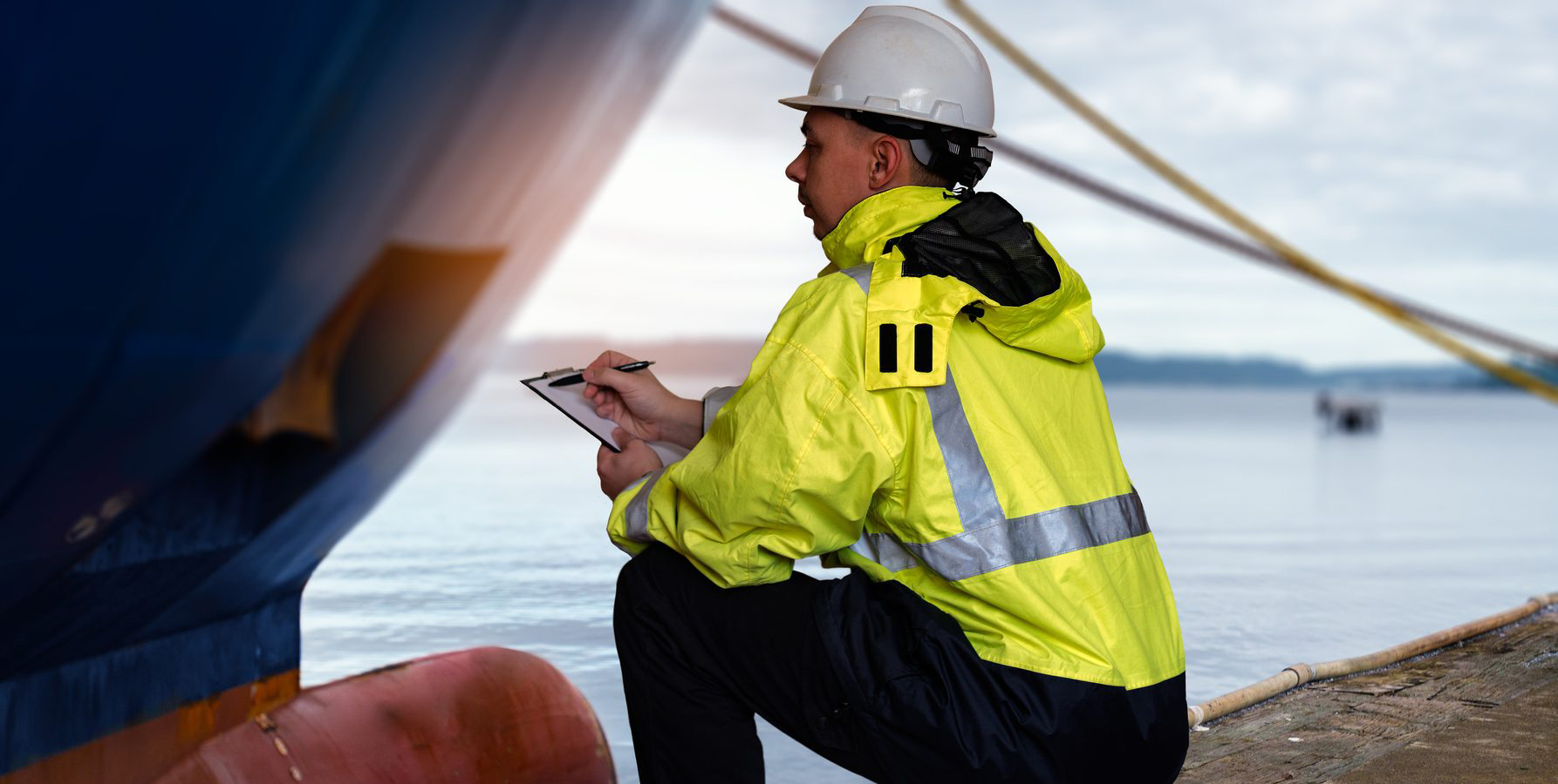 Ship supervisor engineer inspector stands at the dockside in a port. Wearing safety helmet and yellow vest. Cargo shipping industry. Protection and indemnity concept.
