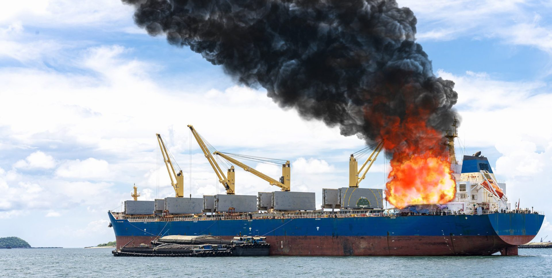 Large general cargo ship for logistic import export of goods, large fire on board billowing